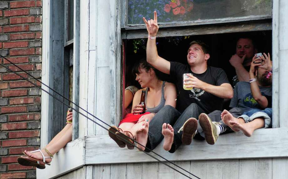 People watch the Main Stage from an apartment on 10th and East Pike. Photo: LINDSEY WASSON / SEATTLEPI.COM