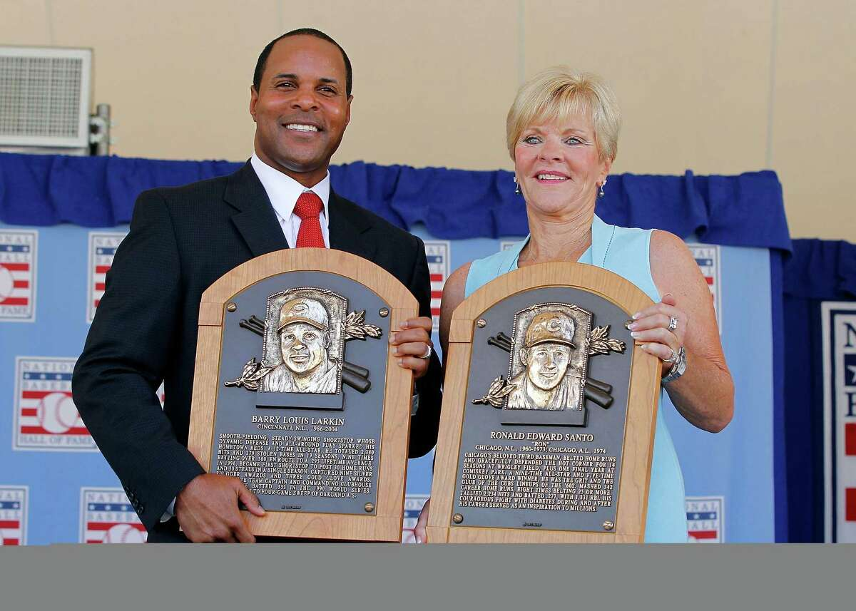 COOPERSTOWN, NY - JULY 22: Barry Larkin and Vicki Santo, widow of inductee Ron Santo, pose for a photo with their plaques at Clark Sports Center during the Baseball Hall of Fame induction ceremony on July 22, 2012 in Cooperstown, New York. Larkin played his entire 19 year major league career with the Cincinnati Reds, compiling a .295 average, 2,340 hits, 1,329 runs, 198 home runs, 960 runs batted in and stole 379 bases. He was named to 12 All-Star games and was the 1995 National League MVP. Larkin was also a member of the 1990 World Series championship team. Santo was named to nine All-Star games in his 15 major league seasons, 14 of which he played for the Chicago Cubs. He finished his career with 2,254 hits, 1,331 runs batted in, 342 home runs and won 5 consecutive gold gloves at third base from 1964-1968. Santo passed away on December 2, 2010.