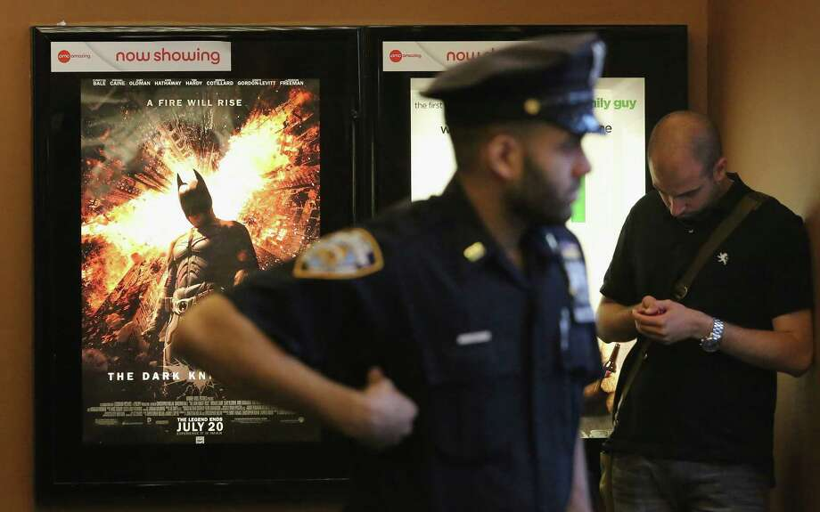 NEW YORK, NY - JULY 20:  An NYPD officer keeps watch inside an AMC move theater where the film 'The Dark Knight Rises' is playing in Times Square on July 20, 2012 in New York City. NYPD  is maintaining security around city movie theaters following the deadly rampage by a gunman inside a Colorado screening of 'The Dark Knight Rises' early this morning. Photo: Mario Tama, Getty Images / 2012 Getty Images
