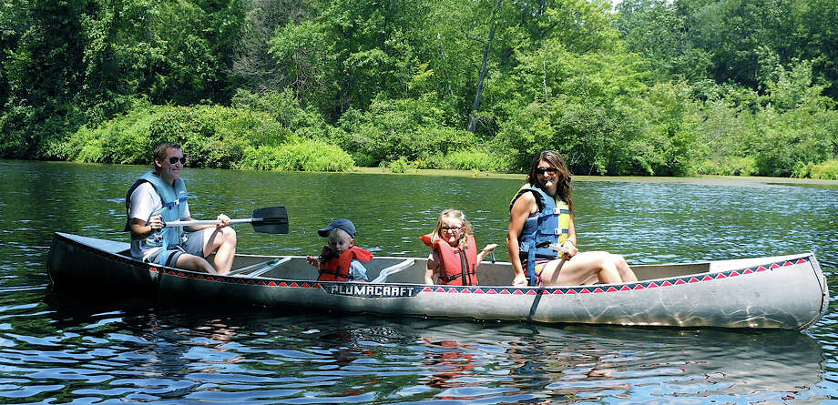 The Gerber family of Westport enjoys a paddle around on the Saugatuck River at the Westport Weston Family Y's Camp Mahackeno on Sunday. Photo: Mike Lauterborn / Westport News contributed