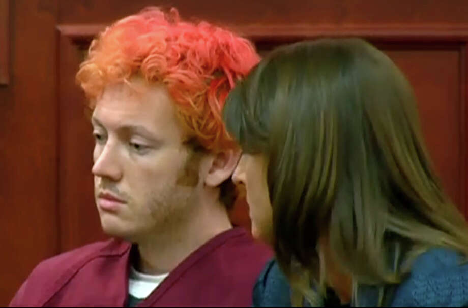 In this image taken from video provided by KUSA.com, James Holmes, left, the suspected gunman in Friday's Colorado theater massacre, makes his first appearance in court with his attorney in Aurora, Colo., Monday, July 23, 2012. (AP Photo/KUSA.com) Photo: Uncredited, TEL