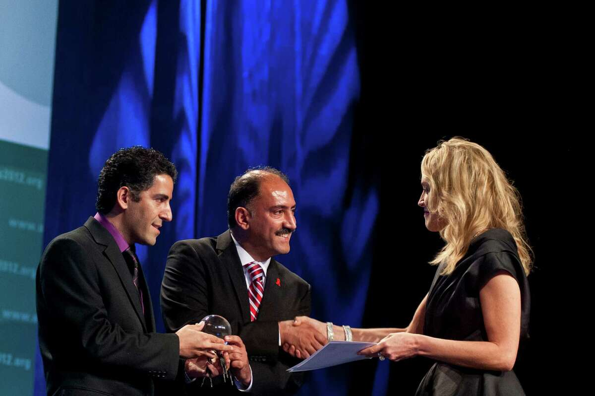 Sharon Stonepresents the inaugural Elizabeth Taylor Award to brothers Dr. Arash Alaei and Dr. Kamiar Alaei on the opening day of the AIDS 2012 - XIX International AIDS Conference at the Walter E. Washington Convention Center on July 22, 2012 in Washington, DC. (Kris Connor/Getty Images)