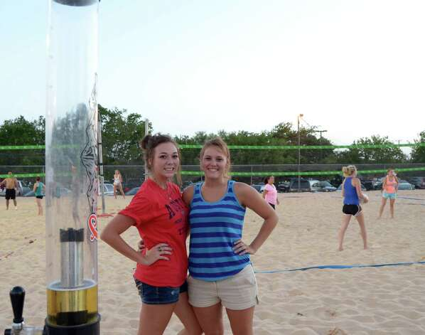 Staci Faust (cq) (left) and Tara Forsberg (cq) have their beer tower and get their sand volleyball fix at Sideliner's on July 20, 2012. Robin Johnson Photo: Robin Johnson