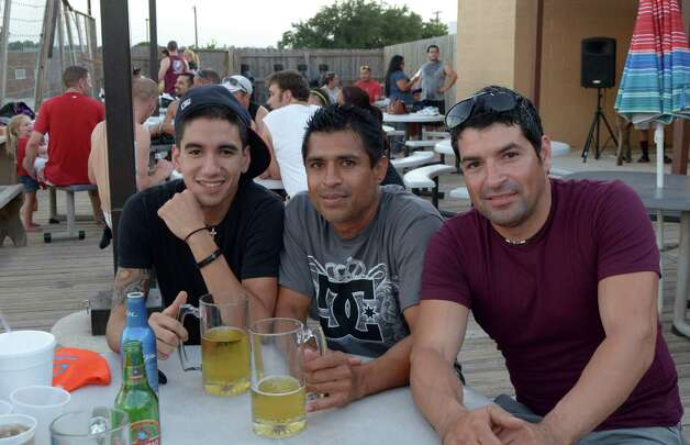 Charles Garcia (from left), Armando Lopez and Sonny Garcia drink it up and watch sand volleyball at Sideliner's on July 20, 2012. Robin Johnson Photo: Robin Johnson