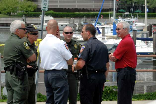 Officials wait at Czescik Municipal Marina in Stamford, Conn. on Monday July 23, 2012 for news of Keith Morris, a New Rochelle, N.Y. firefighter whose boat capsized late Sunday night after it rammed into the harbor's east breakwall and flipped. Photo: Dru Nadler / Stamford Advocate Freelance