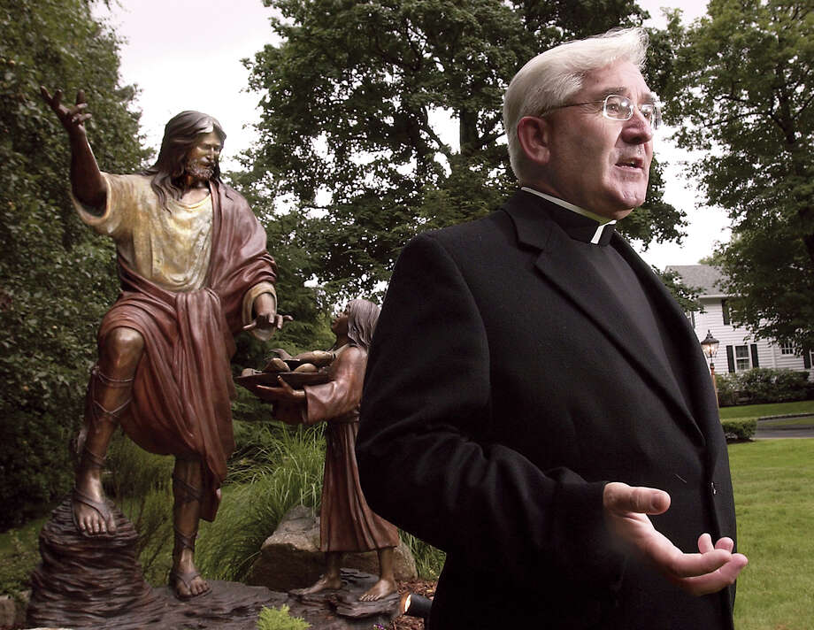 Father Michael Moynihan on the grounds of St. Michael the Archangel Parish in Greenwich in 2003. Moynihan, who resigned in 2007 as pastor of the church, was sentenced Monday, July 23, 2012 in New Haven to serve prison time after pleading guilty last year to obstructing a federal investigation. Photo: Bob Luckey, GT