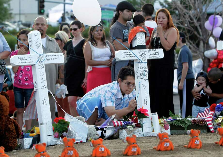 Blennes Quientana writes a message on a cross at a memorial for the victims in the shooting across the street from the Century 16 movie theater in Aurora, Colo., Sunday, July 22, 2012. James Eagen Holmes has been charged in the shooting at the Aurora theater early Friday that killed twelve people and injured more than 50. Photo: AP