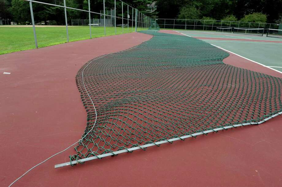A portion of the fence around the tennis courts in Binney Park in Old Greenwich were damaged last week in a storm. The fence, seen here Monday, July 23, 2012, could be repaired as early as Tuesday, July 24, 2012, according to a town official. Photo: Helen Neafsey / Greenwich Time