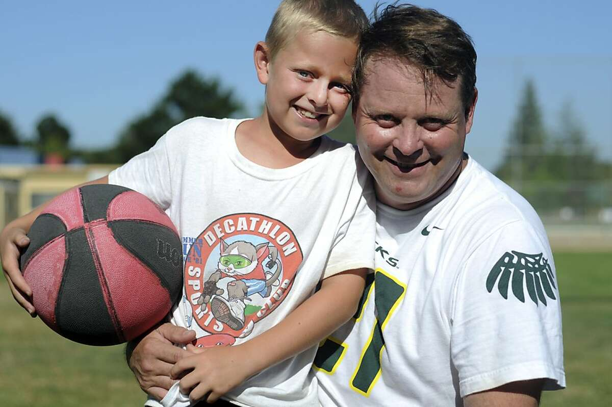 Ken Flax, Olympic hammer-thrower, is photographed with his son Austin, 9, in Los Altos, Calif., July 20, 2012. Flax competed in the 1988 and 1992 Olympic Games.