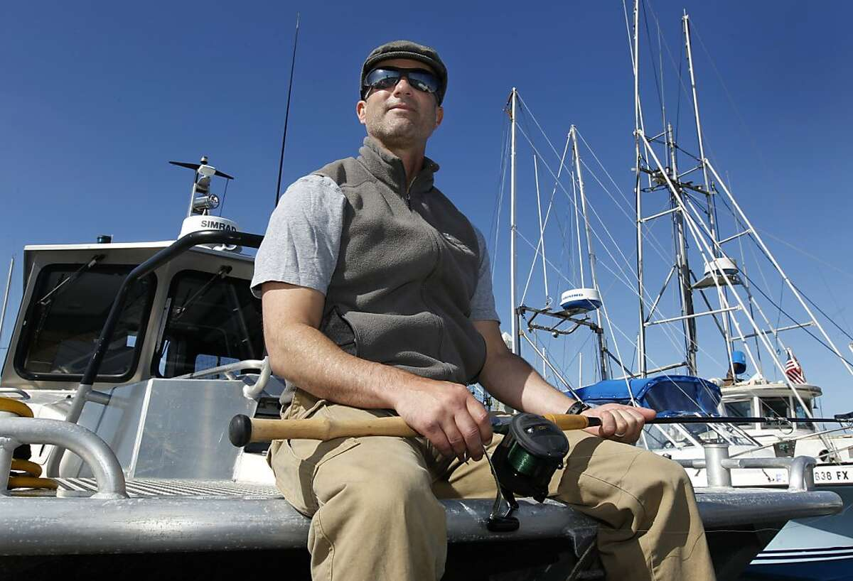 Former Olympian Tom McGuirk prepares his equipment for a day of fishing on his boat,