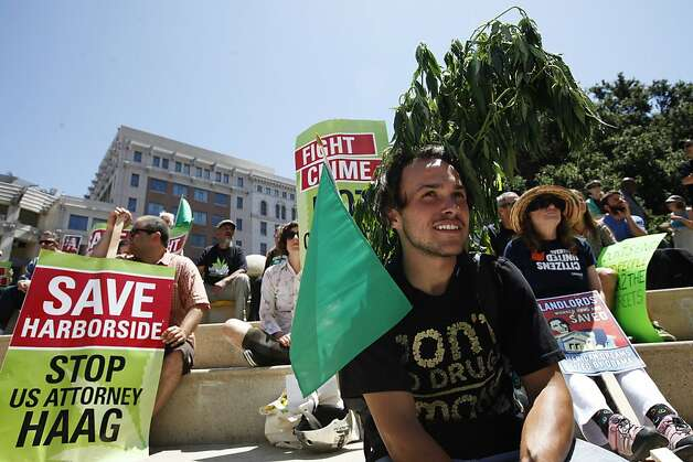 Josh Hewitt, center, joins other protesters at Frank Ogawa Plaza in Oakland, Calif. on Monday, July 23, 2012, as they await the arrival of President Barack Obama. Photo: Sonja Och, The Chronicle