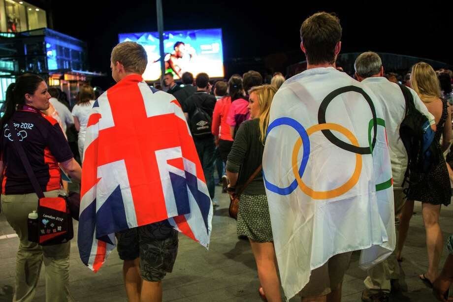 Spectators draped in British and Olympic flags depart a rehearsal for the opening ceremonies in preparation for the 2012 Summer Olympics on Monday, July 23, 2012, in London. Photo: Smiley N. Pool, Houston Chronicle / © 2012  Houston Chronicle