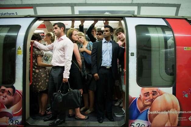 "Commuters wait in a packed London Underground train during a service delay on Monday, July 23, 2012. Numerous delays and failures snarled many of London's public transit lines during both the morning and evening commutes on Monday, frustrating passengers and fueling their worries that the system won't be able to keep up during the games. These travelers were left waiting during a long delay due to a stuck train two stations ahead, while automated announcements over the station's public address system stated that ""there is good working service operating on all London Underground lines."" Photo: Smiley N. Pool, Houston Chronicle / © 2012  Houston Chronicle"