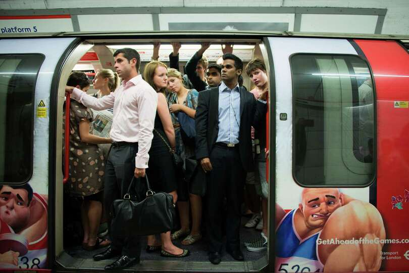 Commuters wait in a packed London Underground train during a service delay on Monday, July 23, 2012.