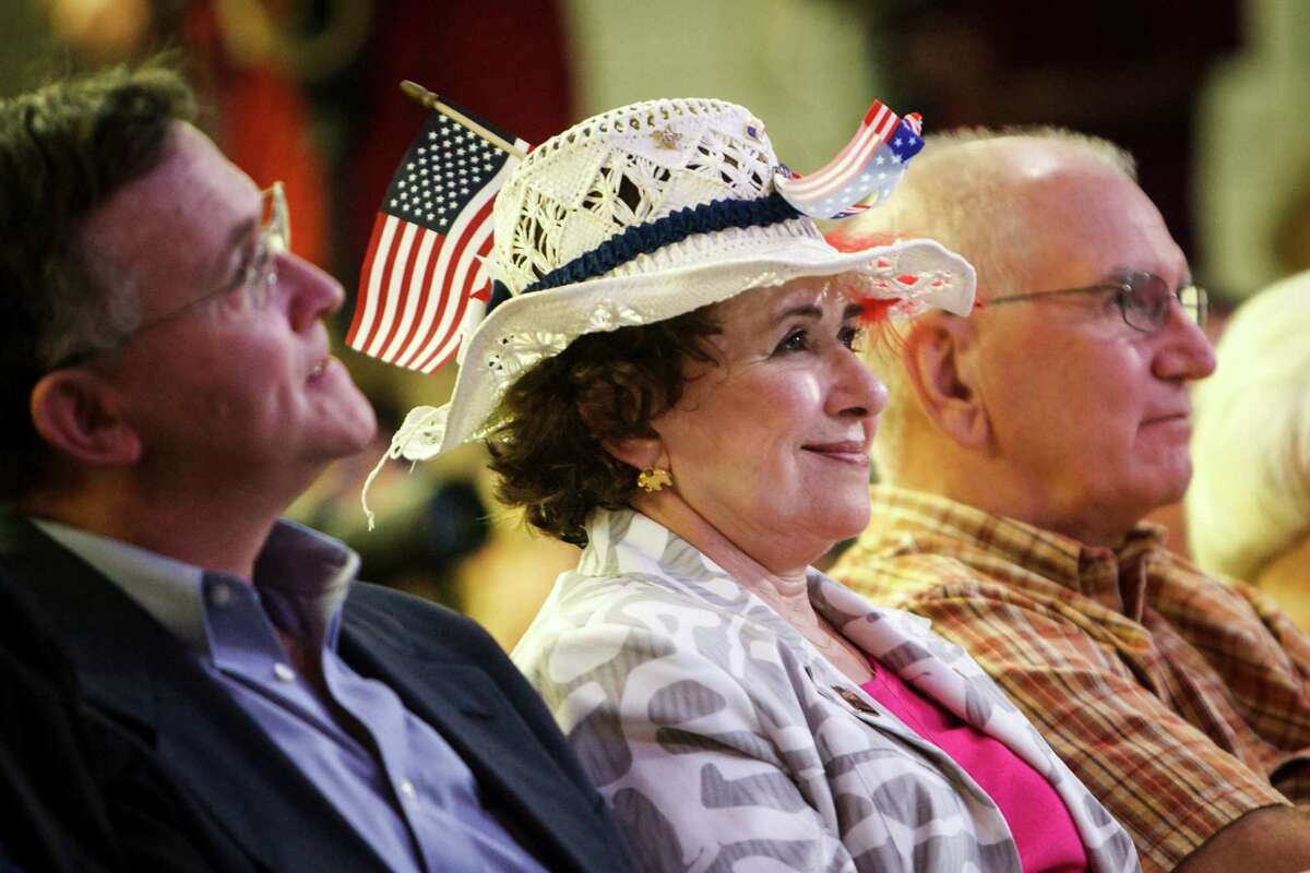 Dee Rowland, center, watches as Republican U.S. Senate candidates former state Solicitor General Ted Cruz and Lt. Gov. David Dewhurst debate each other at the King Street Patriots event hall, Monday, July 23, 2012, in Houston. The two Republican candidates for the U.S. Senate have repeatedly torn into each other during a third debate as early voting began across Texas.
