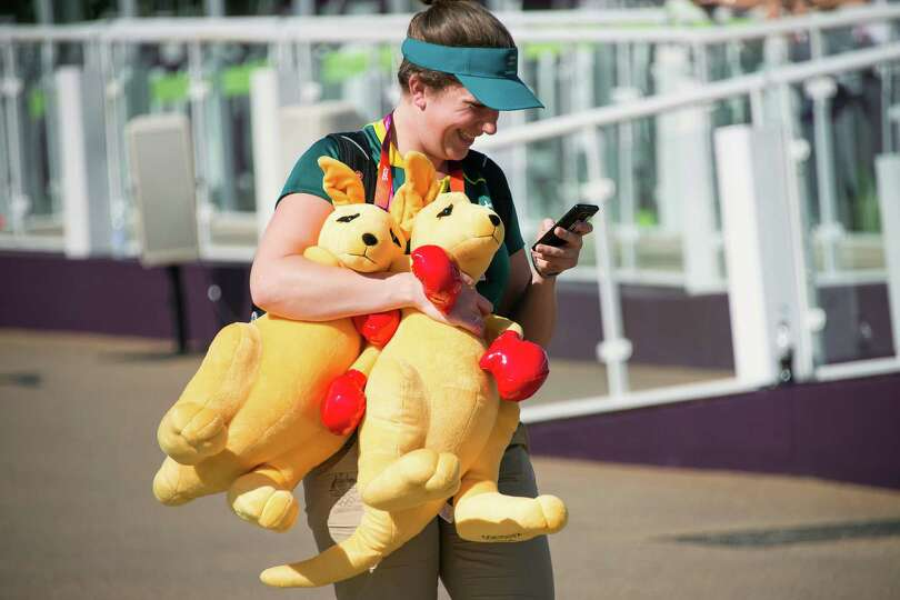 A member of the Australian team carries two of the Aussie boxing kangaroo mascot while walking throu