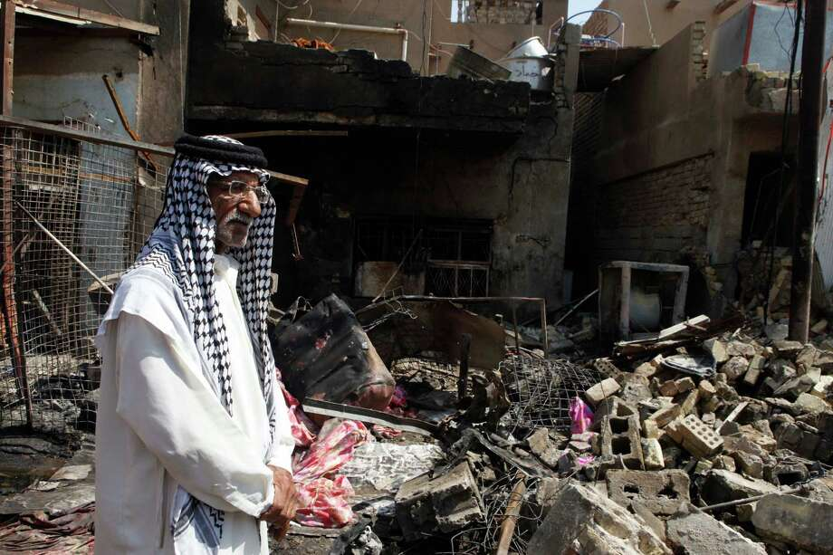 A man stands in front of the scene of a bomb attack in Madain, about 15 miles (25 kilometers) southeast of Baghdad, Iraq, Monday, July 23, 2012. An onslaught of bombings and shootings killed scores of people across Iraq on Monday, in the nation?s deadliest day so far this year. The attacks come days after the leader of al-Qaida in Iraq declared a new offensive seeking to re-assert its might in the security vacuum left by the departing Americans. (AP Photo/Karim Kadim) Photo: Karim Kadim / AP