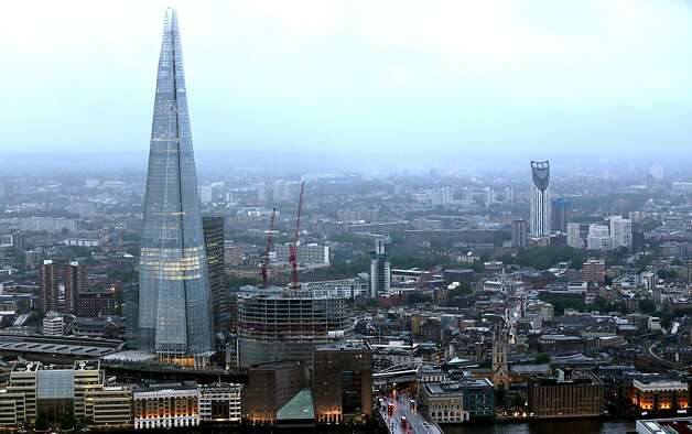 The Shard tower, left, is seen illuminated by lights on the city skyline in London, U.K. on Thursday, July 12, 2012. The 310-meter (1,017 feet) Shard will have a Shangri-La hotel, about 585,000 square feet (53,350 square meters) of office space for which no tenant has been found, 10 luxury apartments and some shops. Photographer: Jason Alden/Bloomberg Photo: Jason Alden, Bloomberg