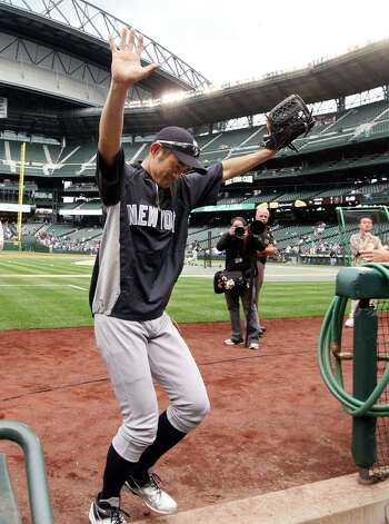 New York Yankees' Ichiro Suzuki waves to fans as he heads into the Yankees' dugout after briefly taking the field before a baseball game against the Seattle Mariners, Monday, July 23, 2012, in Seattle. The Mariners announced earlier in the day that Suzuki, who has played with the Mariners since 2001, was traded to the Yankees. (AP Photo/Elaine Thompson) Photo: Elaine Thompson