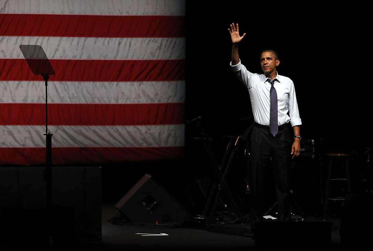 President Obama waves goodbye to the crowd after speaking at a fundraiser at the Fox Theater in Oakland, Calif., Monday, July 23, 2012.