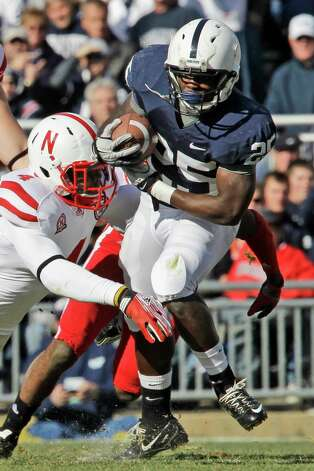 Penn State running back Silas Redd (25) is tackled by Nebraska's Lavonte David (4) during the first quarter of an NCAA college football game in State College, Pa., Saturday, Nov. 12, 2011. (AP Photo/Gene J. Puskar) Photo: Gene J. Puskar, Associated Press / AP