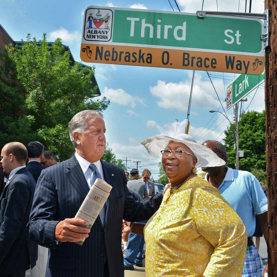 Mayor Jerry Jennings, left, and Nebraska Brace's widow Anne Marie Brace during a ceremony to unveil a street named in Mr. Brace?s honor at the Corner of Lark and Third Streets in Albany Tuesday July 24, 2012.   (John Carl D'Annibale / Times Union) Photo: John Carl D'Annibale / 00018567A