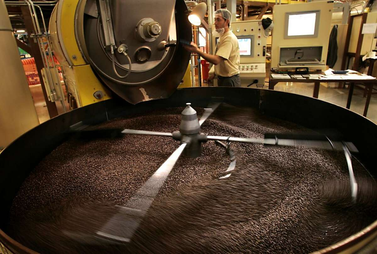 Roaster Eliseo Munoz tends to a freshly roasted batch of coffee beans at the Peet's roasting plant in Alameda.