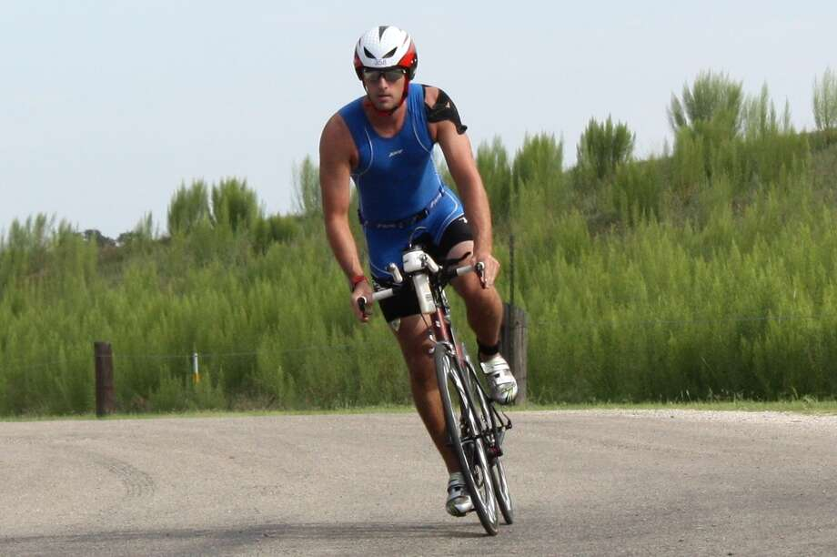 Justin Robinson rounds the bend to the transition area near the end of his bike ride at Sunday's Tiny Texan Triathlon at Boerne City Lake. Robinson finished 16th overall. Photo: Mike Reeder / For The Northwest Weekly