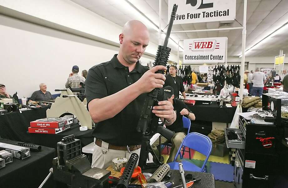 Eric Whiting with Five Four Tactical based out of Fredericksburg, custom builds one of two AR-15 Rifles for a customer Saturday during the Permian Basin Gun Show at the Ector County Coliseum in Odessa, Texas. Under California state law, one of Holmes' guns, a semiautomatic AR-15 rifle, would be illegal. Photo: Cindeka Nealy, Midland Reporter-Telegram