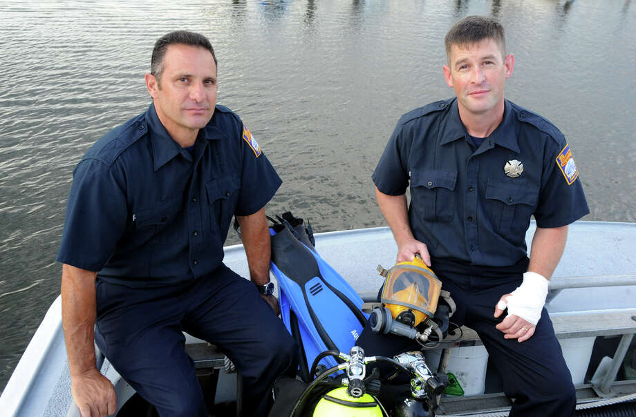 Stamford Fire and Rescue divers Joe Maida, left, and Bill O'Connell on the department's rescue boat docked at Czescik Marina in Stamford, Conn., July 24, 2012.  The two firefighters took part in a rescue operation unlike any in two-decade old Fire Department Dive Team's history Sunday evening when they rescued two people trapped inside a boat that had capsized after striking the seawall at the exit of Stamford Harbor. The driver of the boat, Keith Morris, was killed in the crash. Photo: Keelin Daly / Stamford Advocate