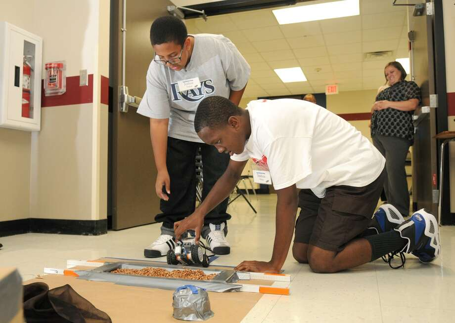 Joshua Trahan, left, a seventh-grader at Claughton Middle School and Joshua White, a freshman at Westfield High School, work their Lego robot for its run through the obstacle course during the Lego Robot Camp for Spring ISD middle school students held at Roberson Middle School. Photo: Jerry Baker