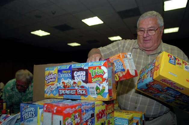 Bill Hamilton, of the Greenwich Unit of the Salvation Army, organizes donated food at the annual Town Hall food drive in July 2010. The Greenwich Service Unit of the Salvation Army will hold its annual food drive at Town Hall from 8 a.m. to 4 p.m. July 26 to benefit food pantries at both Neighbor to Neighbor and the Department of Social Services. Photo: Helen Neafsey, ST / Greenwich Time