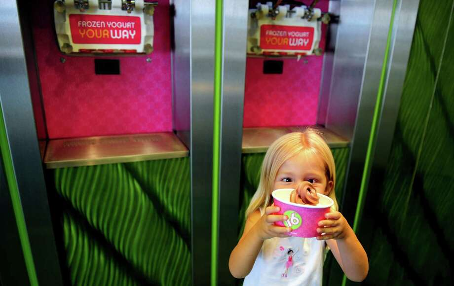 Three-year-old Chloe Gustavson, of Fairfield, eyes her personalized blend of strawberry and chocolate frozen yogurt at 16 Handles in Fairfield, Conn. Tuesday, July 24, 2012.  The self-serve frozen yogurt shop is opening a new location in Stamford. Photo: Autumn Driscoll / Connecticut Post