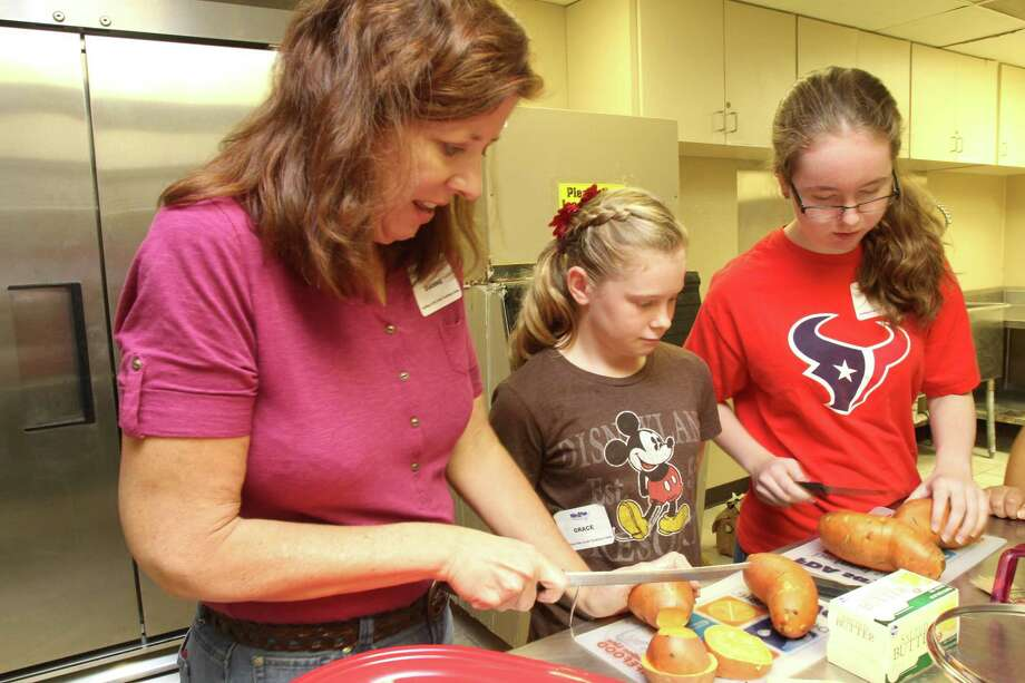 Fort Bend County's extension agent Dianne Gertson shows Grace Mize, 11, of Missouri City, in the center,  and Erin Krusleski, 13, of Sugar Land, how to cut sweet potatoes to grill. Photo: Suzanne Rehak
