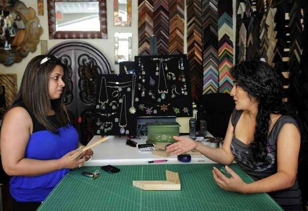 Ana Maria Bars, right, talks to Akansha Kohli about the unusual size of the paintings Kohli had commissioned from an artist in India as they talk at U & I Deco in Stamford on Tuesday, July 24, 2012. Photo: Lindsay Niegelberg / Stamford Advocate