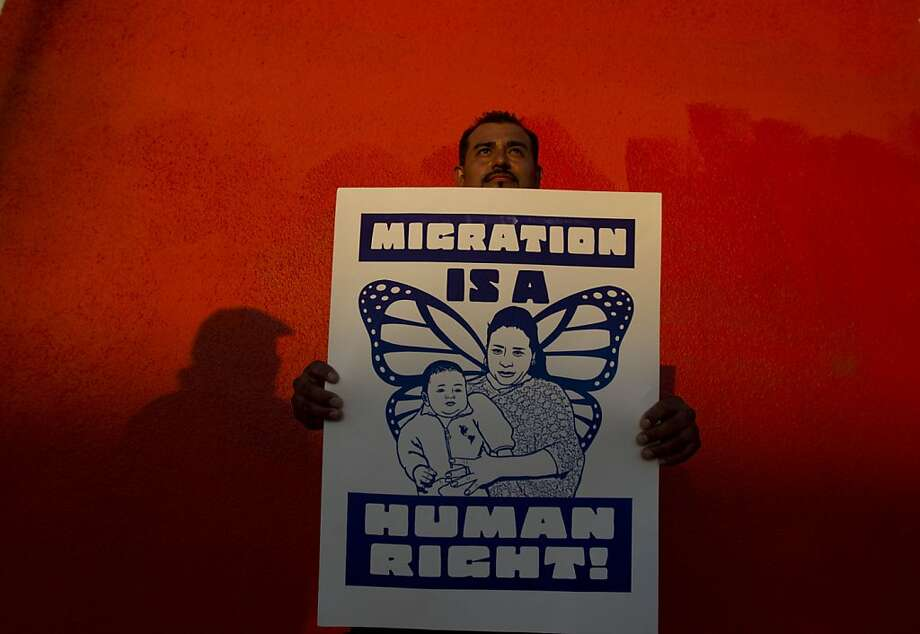 """A protester holds a sign before marching  to the Sandra Day O'Connor Courthouse in downtown Phoenix, before the start of the racial-profiling case against the Maricopa County Sheriff's Office on Tuesday, July 24, 2012. Lawyers who say that Maricopa County Sheriff Joe Arpaio's office disproportionately singled out Latinos in the patrols accused him of launching some sweeps based on emails and letters that don't allege crimes, but complain only that """"dark-skinned people"""" are congregating in a given area or speaking Spanish. Arpaio has long denied racial profiling allegations.  (AP Photo/The Arizona Republic, Nick Oza)  MARICOPA COUNTY OUT; MAGS OUT; NO SALES Photo: Nick Oza, Associated Press"""