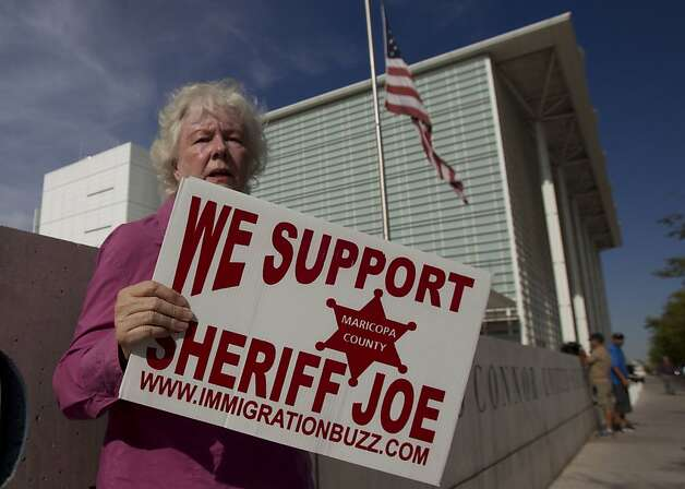 "Kathryn Kodor of Phoenix, holds a sign of support for Sheriff Joe Arpaio at the Sandra Day O'Connor Courthouse in downtown Phoenix, before the start of the racial-profiling case against the Maricopa County Sheriff's Office on Tuesday, July 24, 2012. Lawyers who say that Maricopa County Sheriff Joe Arpaio's office disproportionately singled out Latinos in the patrols accused him of launching some sweeps based on emails and letters that don't allege crimes, but complain only that ""dark-skinned people"" are congregating in a given area or speaking Spanish. Arpaio has long denied racial profiling allegations.  (AP Photo/The Arizona Republic, Nick Oza)  MARICOPA COUNTY OUT; MAGS OUT; NO SALES Photo: Nick Oza, Associated Press"