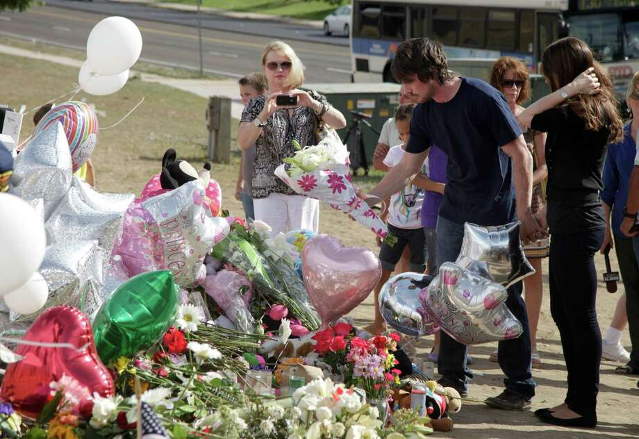 Actor Christian Bale, second right, and his wife Sibi Blazic, right, place flowers on a memorial to the victims of Friday's mass shooting, Tuesday, July 24, 2012, in Aurora, Colo. Twelve people were killed when a gunman opened fire during a late-night showing of the movie Dark Knight Rises, which stars Bale as Batman. Photo: AP