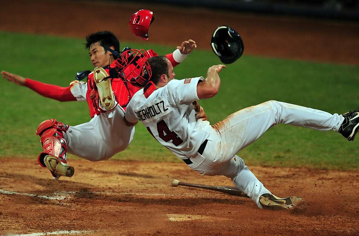 Nate Schierholtz (R) of the US barrells into Chinese catcher Yang Yang (L) to score off a hit by Terry Tiffee in their men's preliminary round baseball game at the Wukesong Baseball Venue during the 2008 Beijing Olympic Games on August 18, 2008. The US won 9-1.