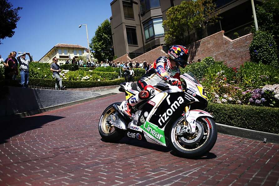 MotoGP motorcycle racer Stefan Bradl navigates his bike down Lombard Street in San Francisco, Calif.