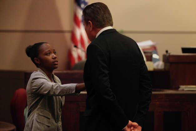 Defendant Tiffany James, 20, demonstrates how the fight escalated as she testifies in her murder trial for the death of Antwan Wolford, the father of her child and her boyfriend at the time, in the Bexar County 399th District Court with defense attorney Bill Reece on Tuesday, July 24, 2012. Photo: Lisa Krantz, San Antonio Express-News / SAN ANTONIO EXPRESS-NEWS