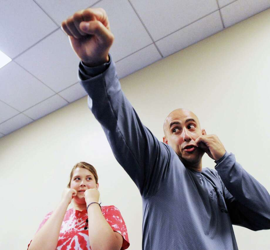 At left, Kimberly Tartaglia, 18, of Greenwich, learns how to throw a punch from Greenwich Police Officer Jeff Morris during a self-defense course for young women at the Greenwich Police Department, Tuesday, July 24, 2012. Photo: Bob Luckey / Greenwich Time