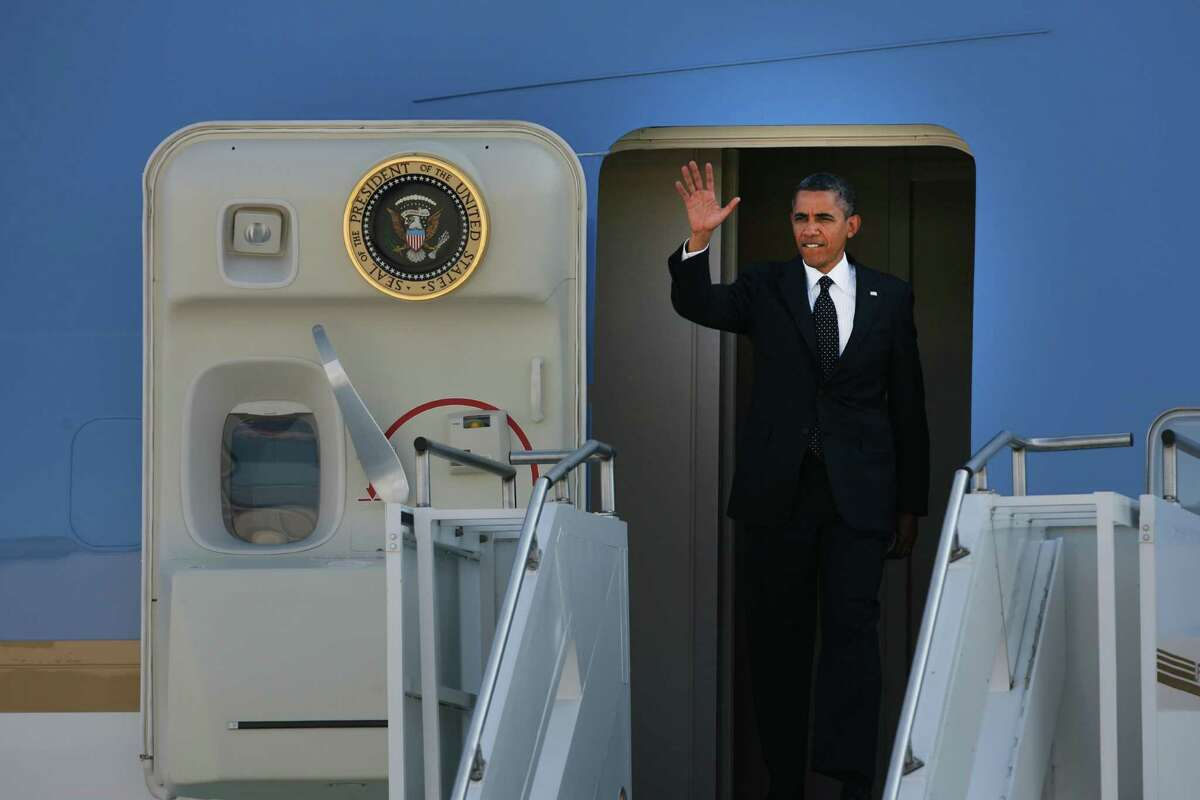 President Obama waves to people gathered on the runway as he exits Air Force One at King County International Airport on Tuesday, July 24, 2012. Obama is in town for the third time this year to raise money at two private fundraising events and will stay overnight in Bellevue before departing Wednesday morning. The two events, one at former Costco CEO Jim Sinegal's house, the other a larger reception of about 200, are expected to contribute around $1.75 million towards Obama's re-election campaign.