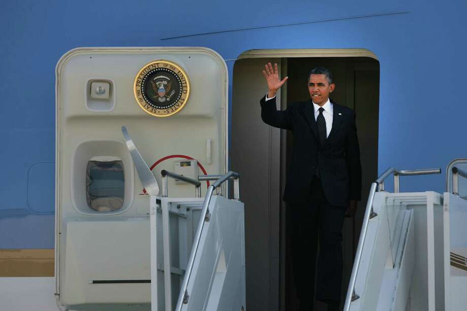 President Obama  waves to people gathered on the runway as he exits Air Force One at King County International Airport on Tuesday, July 24, 2012. Obama is in town for the third time this year to raise money at two private fundraising events and will stay overnight in Bellevue before departing Wednesday morning. The two events, one at former Costco CEO Jim Sinegal's house, the other a larger reception of about 200, are expected to contribute around $1.75 million towards Obama's re-election campaign. Photo: LINDSEY WASSON / SEATTLEPI.COM