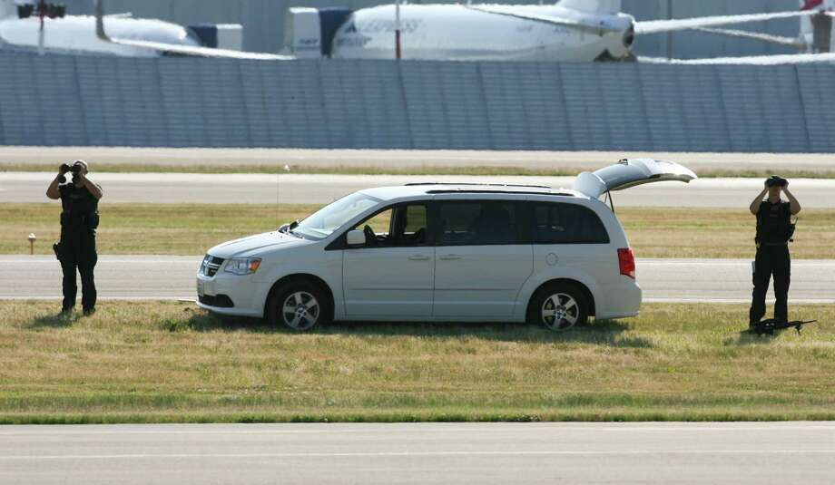 Secret Service snipers monitor the scene with large binoculars as Air Force One taxis to a stop at King County International Airport on Tuesday, July 24, 2012. Obama is in town for the third time this year to raise money at two private fundraising events and will stay overnight in Bellevue before departing Wednesday morning. The two events, one at former Costco CEO Jim Sinegal's house, the other a larger reception of about 200, are expected to contribute around $1.75 million towards Obama's re-election campaign. Photo: LINDSEY WASSON / SEATTLEPI.COM