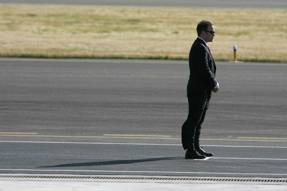 A Secret Service member monitors the scene as Air Force One touches down at King County International Airport on Tuesday, July 24, 2012. Obama is in town for the third time this year to raise money at two private fundraising events and will stay overnight in Bellevue before departing Wednesday morning. The two events, one at former Costco CEO Jim Sinegal's house, the other a larger reception of about 200, are expected to contribute around $1.75 million towards Obama's re-election campaign. Photo: LINDSEY WASSON / SEATTLEPI.COM