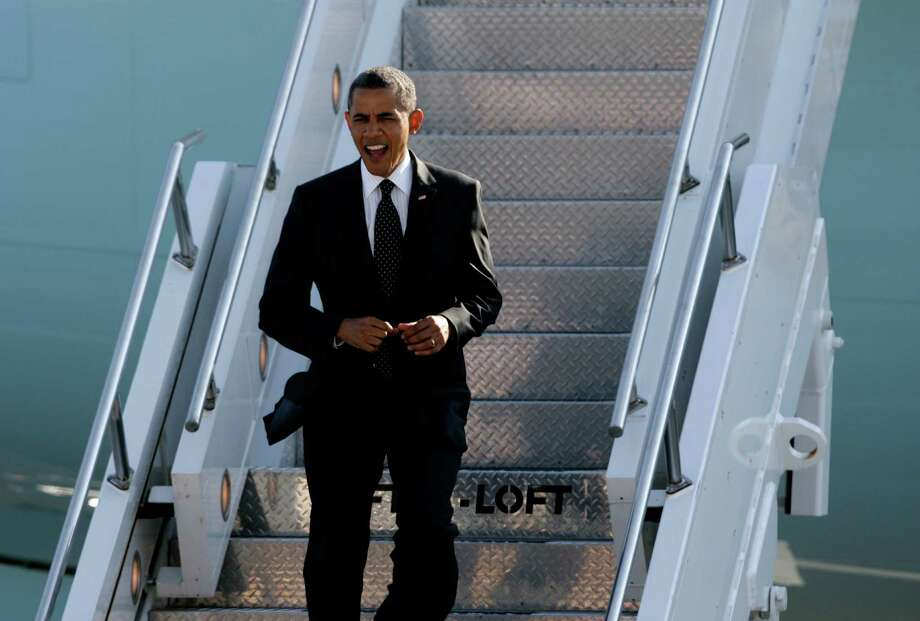President Obama  greets people on the runway as he exits Air Force One at King County International Airport on Tuesday, July 24, 2012. Obama is in town for the third time this year to raise money at two private fundraising events and will stay overnight in Bellevue before departing Wednesday morning. The two events, one at former Costco CEO Jim Sinegal's house, the other a larger reception of about 200, are expected to contribute around $1.75 million towards Obama's re-election campaign. Photo: LINDSEY WASSON / SEATTLEPI.COM