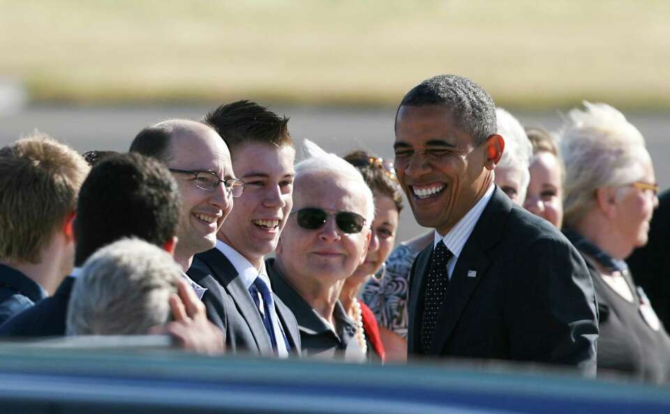 President Obama smiles as he greets people on the runway after exiting Air Force One at King County