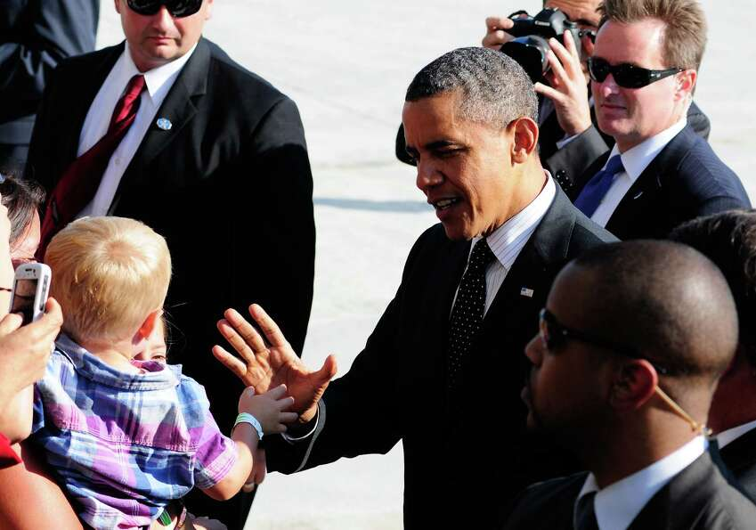 President Obama  high-fives a small child as he greets people gathered on the runway after he arrive