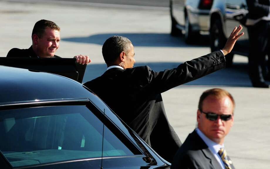 President Obama  waves in the direction of Air Force One as he gets into the Presidential limo at King County International Airport on Tuesday, July 24, 2012. Obama is in town for the third time this year to raise money at two private fundraising events and will stay overnight in Bellevue before departing Wednesday morning. The two events, one at former Costco CEO Jim Sinegal's house, the other a larger reception of about 200, are expected to contribute around $1.75 million towards Obama's re-election campaign. Photo: LINDSEY WASSON / SEATTLEPI.COM